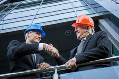 Engineers in helmets shaking hands. Close-up of engineers in helmets shaking hands royalty free stock photos