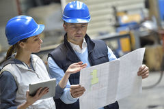 Engineers in industrial factory reading instructions Stock Photos