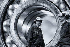Engineers inside giant bearing of titanium royalty free stock image