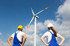 Engineers or installers posing in front of wind energy turbine Royalty Free Stock Image