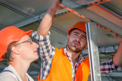 Engineers installing solar panels on frame. Close up view on workers at solar energy station Royalty Free Stock Photo
