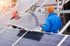 Engineers installing solar panels in winter. Outdoors. Workers are dressed in uniform and warmed with additional clothes Royalty Free Stock Photo
