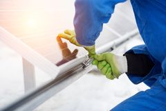 Engineers installing solar panels. Worker with tools maintaining photovoltaic panels. In snow-covered weather. Macro photography Stock Photo