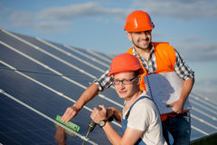 Engineers installing solar panels. Workers with tools maintaining photovoltaic panels Stock Images