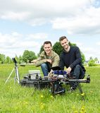 Engineers With Laptop And Digital Tablet By UAV. Portrait of happy male engineers with laptop and digital tablet by UAV at park stock images