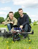 Engineers With Laptop And Digital Tablet By UAV. Portrait of male engineers with laptop and digital tablet by UAV at park stock photography