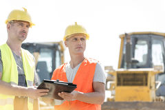 Engineers looking away while holding clipboard at construction site against clear sky Royalty Free Stock Photography