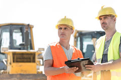 Engineers looking away while holding clipboard at construction site against clear sky Stock Photography