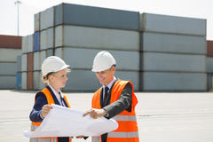 Engineers looking at blueprint in shipping yard Royalty Free Stock Image