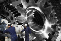 Engineers, mechanics with giant machinery Royalty Free Stock Photos