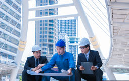 Engineers meeting at terrace on top of construction site. Coworkers discussing. Boss and worker argue. Conversation in team. Wear helmet hold paper plans Stock Photo
