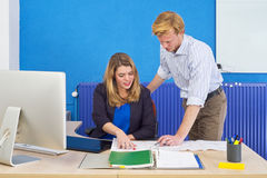 Engineers meeting. Two product engineers discussing technical drawings on a desk in an office Royalty Free Stock Photography