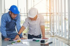 Engineers are meeting, working and looking blueprint at smartphone in the office to discuss.Engineering tools and construction co royalty free stock photography