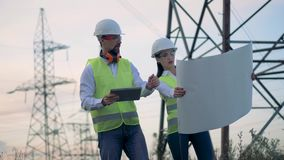 Engineers near electrical substation. Professional electricians with blueprints at electrical substation. 4K stock footage