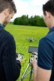 Engineers Operating UAV Helicopter. Rear view of young engineers operating UAV helicopter with remote controls in park stock photo