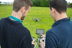 Engineers Operating UAV Helicopter. Rear view of young engineers with remote controls and screen operating UAV helicopter in park stock photo