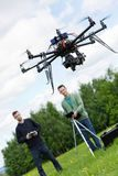 Engineers Operating UAV Octocopter in Park. UAV octocopter flying with young engineers operating it in background at park Stock Image