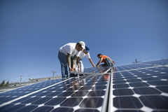 Engineers Placing Solar Panel Against Sky Royalty Free Stock Images