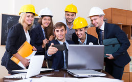 Engineers posing in front of smartphone Royalty Free Stock Photos