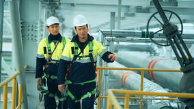 Engineers, in production plant as team discussing, industrial scene in background stock footage