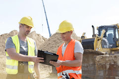 Engineers reading clipboard at construction site against clear sky Royalty Free Stock Images