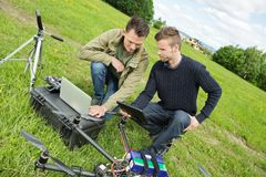 Engineers Repairing UAV Helicopter. Young male engineers discussing over digital tablet and laptop by UAV drone in park stock photography