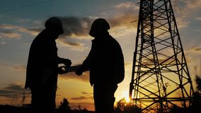 Engineers shaking hands at the construction of high-voltage power. Teams engineer looking discussing plan. Silhouette