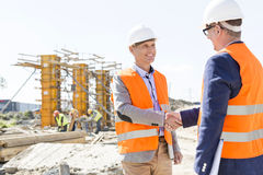 Engineers shaking hands at construction site against clear sky royalty free stock images