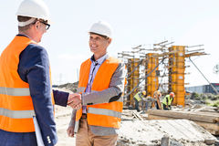Engineers shaking hands at construction site against clear sky Stock Image