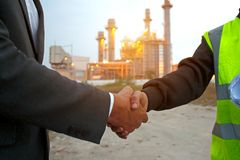 Engineers shaking hands at power plant after success day stock images