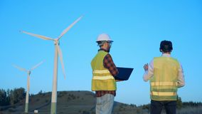 Men use modern devices near windmills, back view. Engineers stand on a field, working with digital devices stock video footage