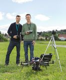 Engineers Standing By UAV Helicopter And Tripod. Happy young engineers standing by UAV helicopter and tripod in park stock image