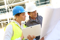 Engineers with tablet and blueprint Stock Photo