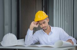 Engineers are thinking about the blueprint at the table. /Young engineers fail to make mistakes in their work and business Royalty Free Stock Photo