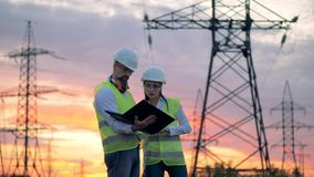 Engineers in uniform working with a laptop near transmission lines. 4K stock footage