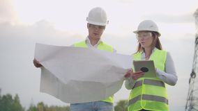 Engineers in uniform working with a laptop near transmission lines.  stock video footage