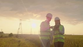 Engineers in uniform working with a laptop near transmission lines.  stock video