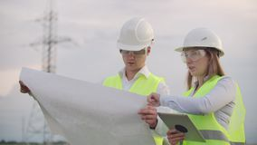 Engineers in uniform working with a laptop near transmission lines.  stock footage