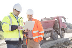 Engineers using laptop at construction site against clear sky on sunny day royalty free stock photos