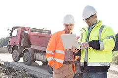 Engineers using laptop at construction site against clear sky on sunny day Royalty Free Stock Images