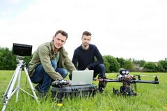 Engineers Using Laptop By UAV Helicopter. Portrait of young engineers using laptop by UAV helicopter and tripod at park royalty free stock photo
