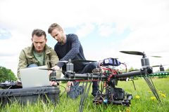 Engineers Using Laptop By UAV Octocopter. Young male engineers using laptop by UAV octocopter in park Royalty Free Stock Images