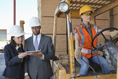 Engineers using tablet PC with female industrial worker driving forklift truck Royalty Free Stock Images