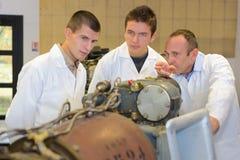 Engineers viewing mechanical exhibit. Engineer stock images