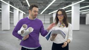 Engineers walk in a room and discuss a working plan, holding blueprints in hands. 4K stock video footage