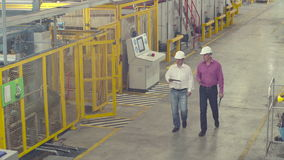Engineers walking through factory. And discussing work stock video