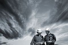 Engineers walking under dark clouds Royalty Free Stock Image