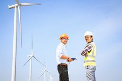 Engineers and wind turbines. Engineers and wind turbines for electricity production royalty free stock photography