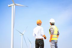 Engineers and wind turbines. Engineers and wind turbines for electricity production stock image