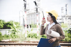 Engineers woman holding radio, blueprint and report schedule for workers security control at power plant energy industry. Royalty Free Stock Photography